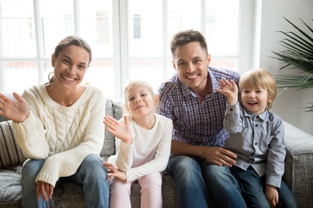 Portrait of happy multi-ethnic family with adopted kids waving hand looking at camera, smiling couple with children sitting on sofa making video call, greeting online by webcam, recording videoblog Foto de archivo - 99706906