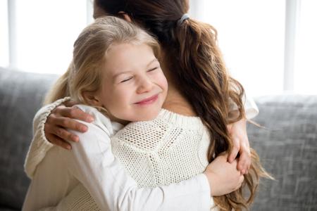 Pequeña hija linda que abraza a la madre que abraza fuerte, a la madre y a la niña feliz en el preescolar o la escuela, abrazando, sonriendo sinceramente a la mamá abrazando a un niño, relaciones cálidas y dulces niños puros amor por el concepto de mamá