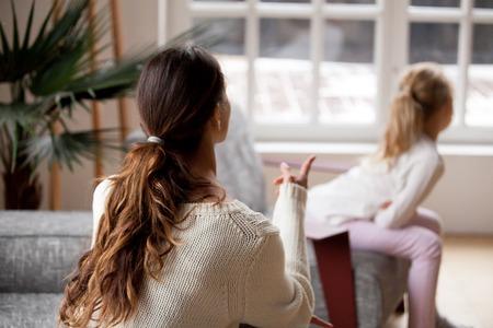 Vista posterior a la madre regañando a la hija, estricta joven madre hablando con el niño reprendiendo a la niña obstinada y ofendida por su mal comportamiento que exige disciplina en el hogar, conflictos familiares y concepto de castigo infantil