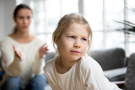 Niña malhumorada, ofendida, enojada, haciendo pucheros, ignorando a la madre que la regaña por su mal comportamiento, su terca hija insultada que no escucha a su madre en desacuerdo con el castigo, los conflictos familiares, el concepto de reprensión infantil