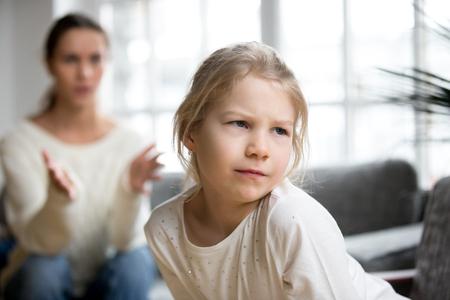 Sulky verärgertes beleidigtes Kindermädchen, das die Mutter ignorierend schilt sie für schlechtes Verhalten, die störrische beleidigte Tochter schmollt, die nicht auf die Mutter hört, die mit Bestrafung nicht einverstanden ist, Familienkonflikt-Kinderzurechtweisungskonzept