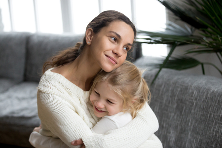 Loving single mother hugging cute little daughter showing love care support, happy woman embracing preschool girl at home, mum and kid sincere warm relationships, new mom for adopted child concept 写真素材
