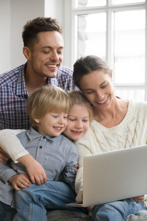 Happy family with adopted kids having fun using laptop together sitting on sofa, parents and son daughter relaxing at home with computer, smiling couple with children watching video online, vertical