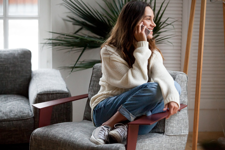 Happy cheerful young woman talking on the phone at home, smiling teen girl making answering call by cellphone sitting on chair, beautiful lady having pleasant funny conversation speaking by mobile Stock fotó