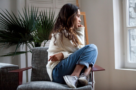 Sad thoughtful teen girl sits on chair feels depressed, offended or lonely, upset young woman suffers from abuse, harassment or heartbreak, grieving lady or violence victim has psychological problem