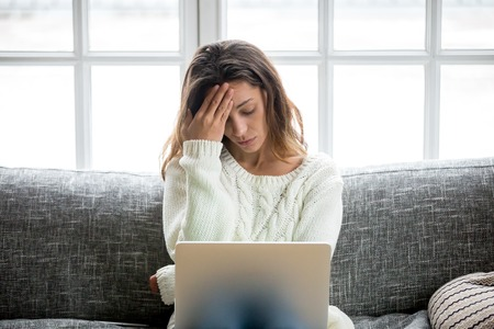 Frustrated sad woman feeling tired worried about problem sitting on sofa with laptop, stressed depressed girl troubled with reading bad news online, email notification about debt or negative message 写真素材