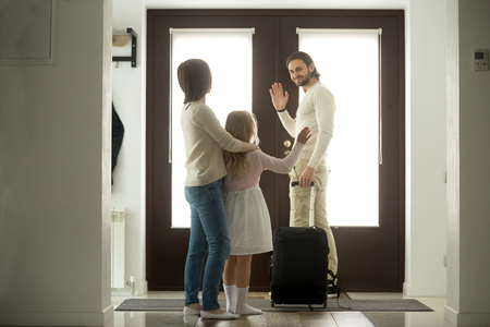 Smiling father waves goodbye to wife and daughter leaves home for business trip stands at door with travel suitcase, kid girl stays with mom seeing off dad moving out after divorce, family separation