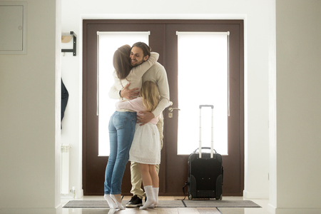 Happy dad hugging family tight arriving from long business trip with suitcase, smiling loving father embracing wife and daughter standing in house hall, welcome back home daddy and reunion concept