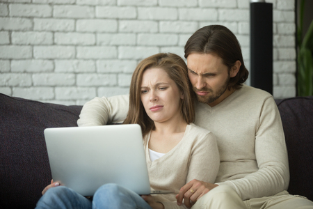 Young couple looking on laptop feeling confused by reading online news browsing internet, annoyed man and woman frowning bewildered by computer problem, reacting on watching disgusting video at home