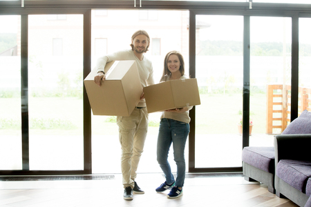 Portrait of happy couple carrying boxes moving into new home, smiling property owners renters looking at camera standing at glass door in hallway, family relocating, mortgage and rental house concept