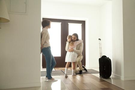 Kleines Kind, das Vater umarmt, der die Familie verlässt, die mit Reisekoffer auszieht, traurige Tochter, die Vater im Haushalle umarmt, der Abschied von Papa weggeht, unglückliches Kind des geschiedenen Elternkonzepts