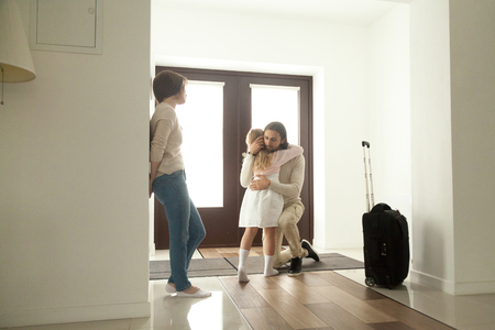 Little kid girl embracing dad leaving family moving out with travel case, sad daughter hugging father in house hall saying goodbye to daddy going away, unhappy child of divorced parents concept