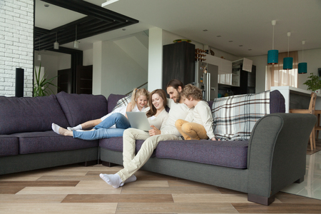 Smiling parents with kids having fun with laptop in cozy living room interior, couple with children son and daughter using computer on sofa at home, happy family relaxing together shopping online