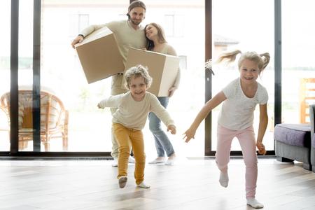 Divertenti bambini felici che corrono nella nuova casa il giorno del trasloco, bambini eccitati ragazzo e ragazza giocano nella grande stanza moderna di lusso mentre i genitori sorridenti entrano nella propria casa, mutuo familiare e concetto di trasferimento