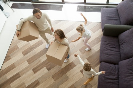 Family and kids enjoy moving day entering new home, happy parents carry boxes with belongings while excited children play together in luxury living room, relocation into big house concept, top view