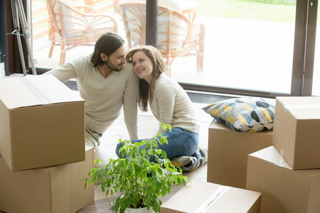 Young smiling couple bonding sitting on floor in new home with boxes on moving day, happy homeowners or renters just moved into modern house with terrace, family relocation, delivery service concept Stock Photo