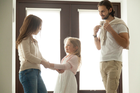 Caring mother helping little daughter dressing for walk with dad, family talking getting ready to go out standing in house hall, divorced young couple shared parenting and joint custody concept