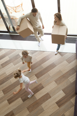 Children playing having fun exploring luxury living room while parents holding boxes entering house on moving day, happy family with kids son and daughter relocating into new home, vertical top view