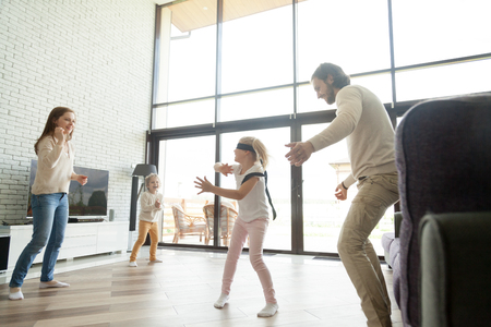 Happy parents play hide and seek with kids in big luxury country house with glass wall, blindfolded girl having fun with mom dad and little brother at home in living room, family active game concept