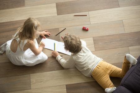 Kinderen zus en broer spelen tekening samen op warme houten vloer in de woonkamer, creatieve kinderen jongen en meisje plezier thuis, broers en zussen vriendschap, vloerverwarming concept, bovenaanzicht