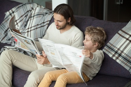 Cute kid son holding newspaper sitting on sofa with dad, curious funny clever boy pretending reading news copying father on weekend, happy daddy enjoying spending time having fun with child at home 写真素材