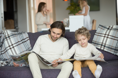Little son pretending reading newspaper sitting on couch with father, cute funny kid imitating dad to be alike spending weekend with family, child boy learning to read discussing news with daddy Foto de archivo - 100266901