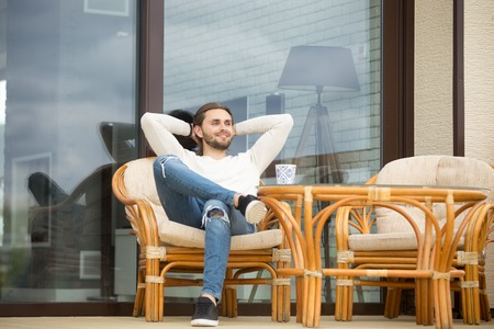 Smiling young relaxed man enjoying pleasant morning sitting on rattan chair on terrace outdoor, happy successful businessman rests outside luxury house in peaceful place, stress free weekend concept Stock fotó