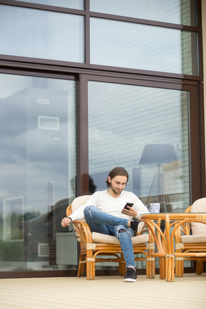 Relaxed man using smartphone sitting outdoor on luxury house terrace chair, young guy resting enjoying weekend outside on fresh air holding mobile phone texting or entertaining online, vertical view