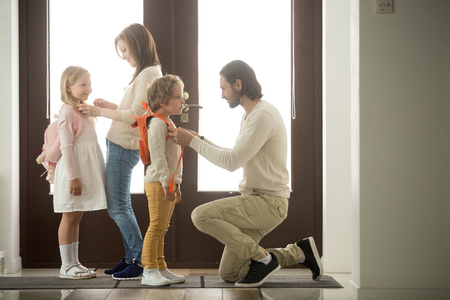 Caring parents helping happy kids put backpack on preparing go to school standing at house hall together, loving family mom and dad dressing getting children son daughter ready in the morning at home