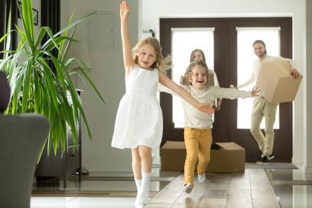 Excited funny kids boy and girl running inside luxury big modern house on moving day, cute children entering exploring new home, happy young family buying real estate, mortgage and relocation concept Stok Fotoğraf