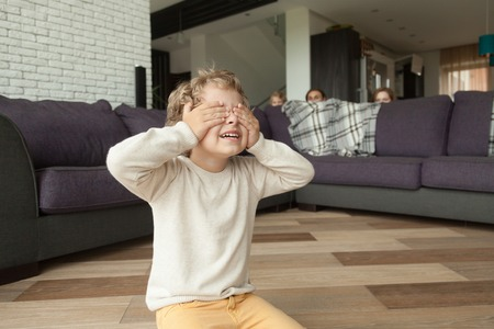Kid boy playing hide and seek game at home, child closing eyes with hands counting while parents and sister hide behind sofa in living room peeking out, happy family having fun with children concept Stock fotó