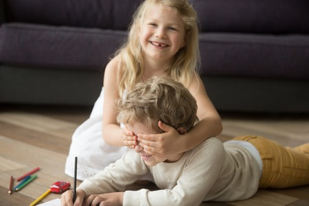 Happy cute siblings enjoying playing peek a boo, kid girl sister laughing closing brothers eyes with hands while child boy drawing on warm wooden floor, children having fun at home together concept Stockfoto