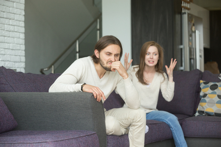 Angry man feels indignant about hysterical girlfriend complaining of bad relationships, frustrated annoyed husband sitting on sofa ignoring wife blaming shouting at him, couple disagreement concept 스톡 콘텐츠