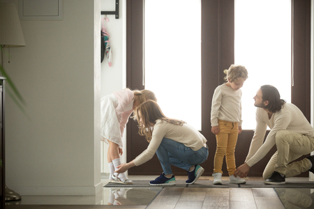 Parents helping children son and daughter put shoes on or take off in hall getting ready to go out together or coming back home from walk, care and good relations in happy family with kids concept