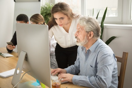 Female executive teaching senior colleague explaining computer work, corporate teacher helping focused aged manager with online task, young woman boss giving instructions to old employee at workplace Stok Fotoğraf - 100709992