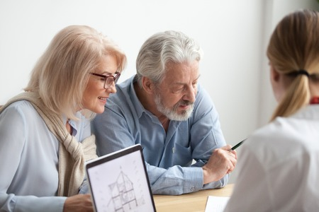 Older couple reading contract at meeting with real estate agent considering new home purchase,    bank worker consulting senior family about buying house loan with project plan on laptop