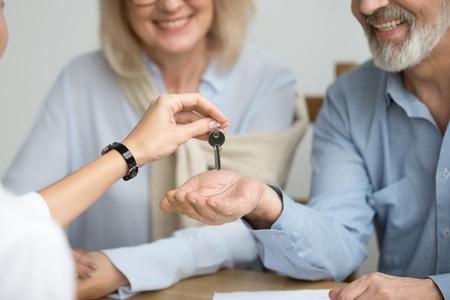 Agent immobilier donnant la clé de couple senior à la nouvelle maison lors de la réunion, les propriétaires immobiliers plus âgés heureux font un concept d'accord d'achat, une famille âgée souriante a acheté ou loué un appartement, vue rapprochée des mains
