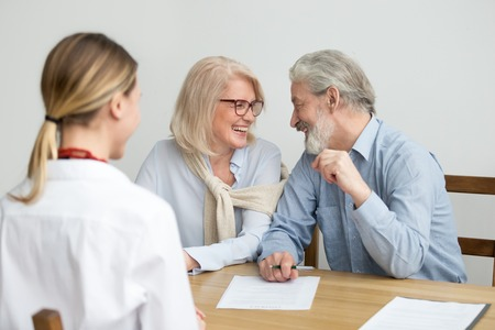 Happy aged couple talking laughing ready to sign document at meeting, senior retired clients buying medical health life insurance, older family make deposit investment in bank with financial advisor Stock Photo