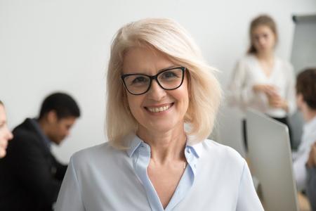 Porträt der lächelnden älteren Geschäftsfrau, die Brille mit Geschäftsleuten am Hintergrund trägt, glücklicher älterer Teamleiter, weiblicher gealterter Lehrerprofessor oder Chef der Chefin, die Kamera, Kopfschuss betrachtet Standard-Bild