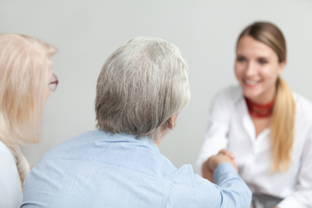 Rear view at senior couple handshaking medical worker visiting doctor, older family and financial advisor or lawyer shaking hands at meeting, happy grey-haired aged elderly clients making deal Stock Photo