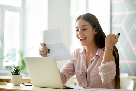 Happy young woman student or employee excited by reading good news in paper letter about new job, great deal, positive exam result, celebrating success or opportunity offered in written notification Stock Photo