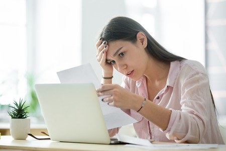 Worried frustrated woman shocked by bad news or rejection reading letter, stressed girl troubled with financial problem, domestic bills or debt, millennial student upset by failed test notification Stock Photo