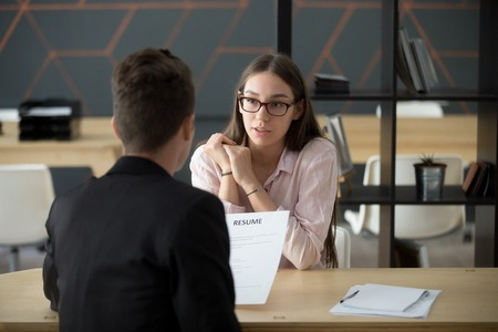 Confident millennial female applicant talking at job interview answering questions, young serious candidate speaking to hr telling about work experience, introduction and first impression concept Фото со стока - 100853422