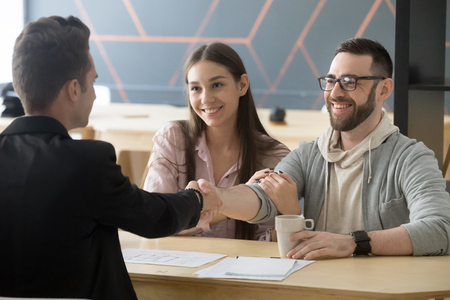 Happy millennial couple handshaking realtor making real estate deal, smiling clients and architect shaking hands, mortgage loan investment contract for new house purchase or construction concept