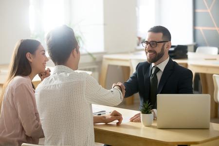 Uśmiechnięty prawnik, pośrednik w handlu nieruchomościami lub doradca finansowy, uścisk dłoni młodej pary dziękującej za poradę, brokerowi ubezpieczeniowemu lub pracownikowi banku i tysiącletnim klientom podają sobie ręce, dokonując transakcji, inwestując lub biorąc pożyczkę Zdjęcie Seryjne