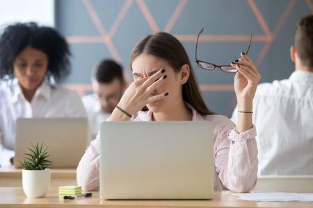 Mujer joven quitándose las gafas cansada del trabajo en la computadora, estudiante o empleado agotado que sufre de tensión ocular o problema de visión borrosa de la computadora después de un uso prolongado de la computadora portátil, concepto de fatiga ocular