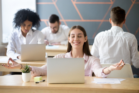 Calm smiling woman practicing office meditation in coworking space taking break for relaxation, mindful happy millennial student or employee feeling zen enjoying no stress free relief at work concept Stock Photo
