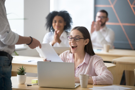 Excited successful student receiving document from boss with good result, colleagues congratulating happy millennial promoted rewarded employee amazed by great news in written notice with applause