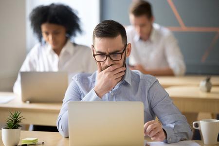 コワーキングオフィスでラップトップで作業するビジネス上の問題を解決することに懸念を抱くオンラインタスクを考える深刻なビジネスマン、悪