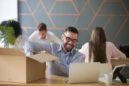Smiling new male employee unpacking box with belongings at workplace, happy hired office worker newcomer on first working day concept, excited millennial businessman put laptop on desk in coworking Stock Photo - 100854175